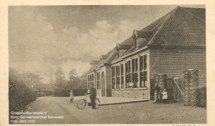 Verleden tussen 1920 en 1930 - Openbare lagere school. De foto is gemaakt in de richting van de Amersfoortsestraat. Deze verbindingsweg stond destijds bekend als het Tweede Achterdorp, Barneveld