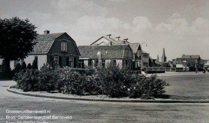 Verleden, 1960 - Lunterseweg. Vooraan een plantsoen. Middenachter de zinkwitfabriek. Op de achtergrond de toren van de Oude Kerk.  - Barneveld