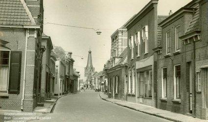 Verleden 1955 - De Langstraat met links het kantoorpand van veevoederfabriek De Heus, iets verder is de zijgevel van schoenenzaak Van der Schans zichtbaar. Rechts de groentenzaak van Kap. In het midden rechts de vakteken- later technische school, nog later werd hier de kledingfabriek Barcon in gevestigd. - Barneveld